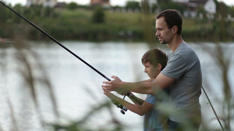 Smiling dad and son fishing and relaxing at pond Footage