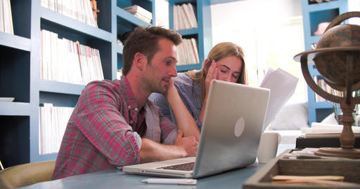 Worried Couple At Desk In Home Office Looking At Bills Live Action