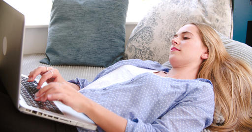 Woman Lying On Couch At Home Using Laptop Live Action