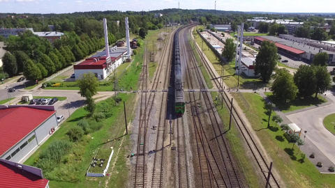 Aerial shot of a freight train passing a station ビデオ