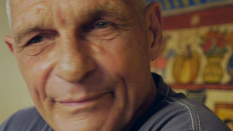 An elderly man goes back and forth from serious to smiling - closeup portrait Footage