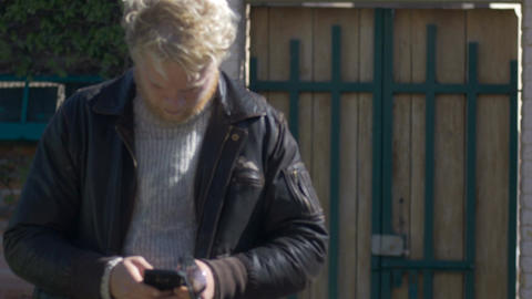 A young millennial man texting on his cell phone outside wearing an open leather Footage