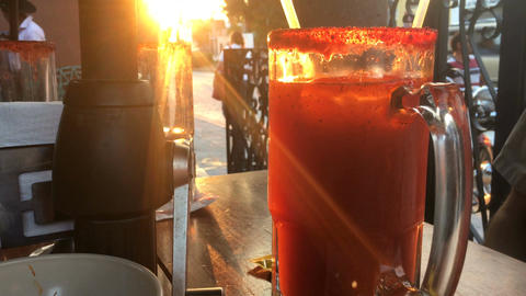 A man stirs a large drink while sitting outside at a cafe during sunset Footage