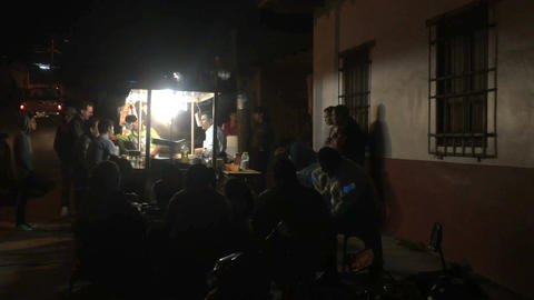 PATZCUARO , MEXICO - CIRCA JULY 2016 - People gather around a taco stand at nigh Footage