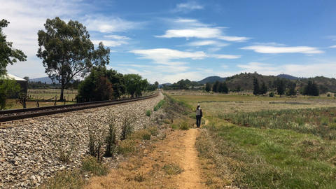 One woman walking along a trail next to the railroad tracks in a rural setting d Footage