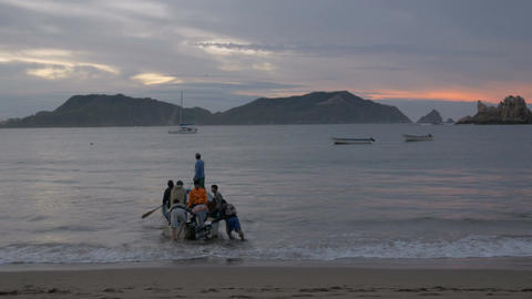 7 men get into a small motor boat from shore and go out towards sea during sunri Footage