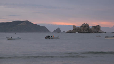 Men prepare their boats for their morning fishing on the ocean as a pelican flie Footage