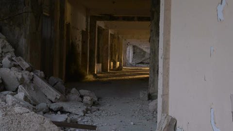 An abandoned hallway with crumbling bricks and debris in a hotel damaged during  Footage