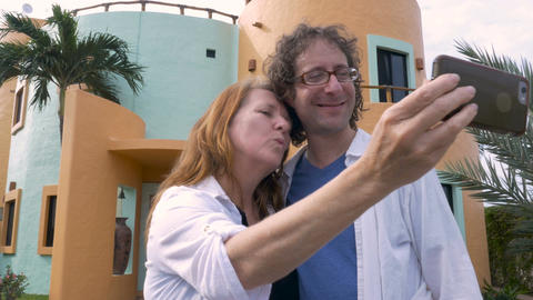 A happy older middle aged couple take selfies in front of their new house and lo Footage