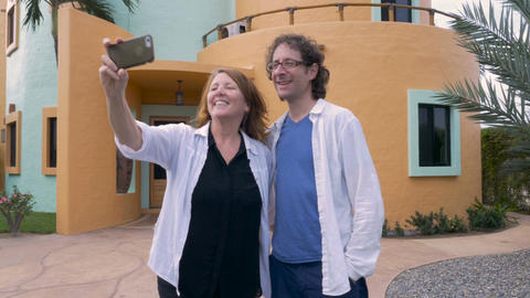 A couple take photos of themselves in front their new house with their cell phon Footage