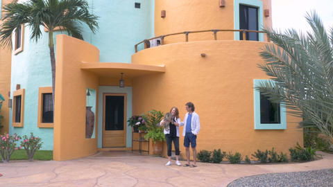 A couple stand in front of their home colorful curved home in the summer, pick u Live Action