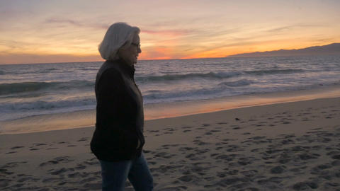 Happy healthy attractive fit mature active retired 60s woman looking at beach su Footage