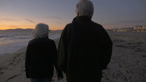 Mature fit active retired 60s couple walking on beach during sunset or sunrise f Footage
