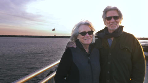 Attractive happy smiling mature 60s couple with US flag in background over ocean Footage