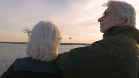Healthy mature 60s adults looking at flag blowing in breeze across water. Retire Footage