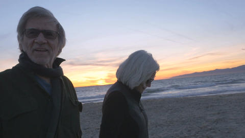 Attractive happy smiling mature 60s couple walking on beach at sunset. Retired f Footage