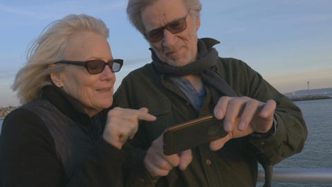 Attractive happy smiling mature couple in 60s using smartphone technology at sun Footage