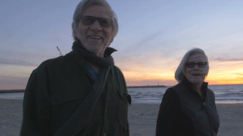 Healthy happy smiling elderly 60s couple walking on beach at sunset. Retired fit Footage