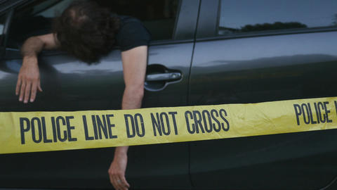 Injured or dead caucasian man hanging out of car crime scene behind police line  Live Action