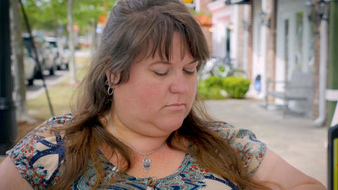 Frustrated impatient irritated plus sized woman waiting outside on sidewalk at a Footage