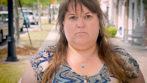 A frightened scared natural plus size woman showing fear while standing outside  Footage