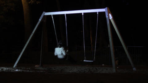 Young girl uses a swing in a park playground into a warm spring evening 8 Footage