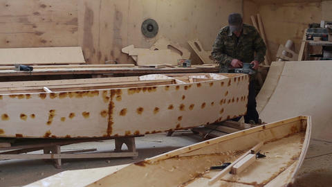 A carpenter polishes details wooden boat at the shipyard Live Action