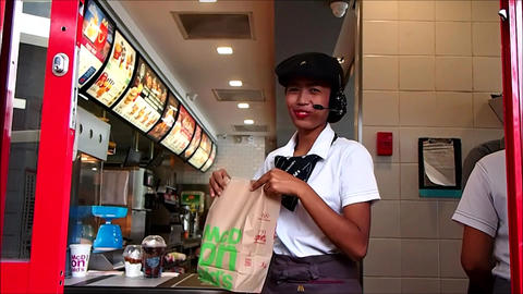 A fast food chain worker serves food to a customer at a drive thru window Live Action