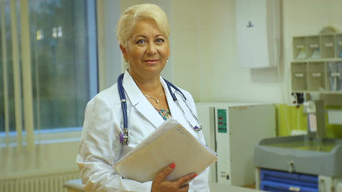 Middle-aged Woman Doctor with Stethoscope Stands in Ward Footage