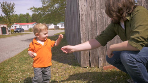 A small trusting young toddler takes a flower from his millennial hipster father Footage