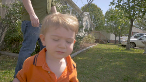 A cute young toddler boy walking outside with his father looks at the camera in  Footage