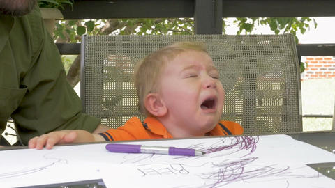 A father hands a marker to his crying frustrated tired young blond child boy in  Live Action