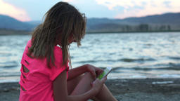 The little girl is sitting near the water and Playing The smartphone Footage