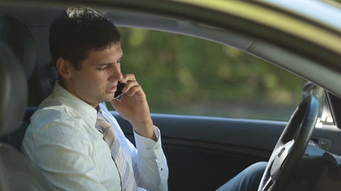 Busy business executive talking on phone in car Live Action