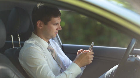 Entrepreneur surfing net on phone in car Live Action