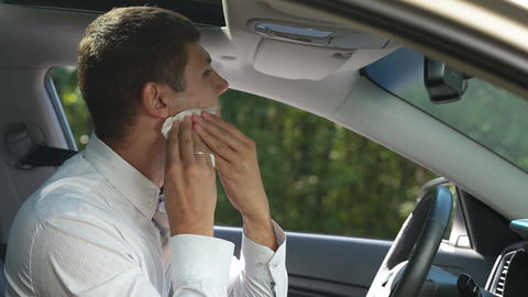 Businessman cleaning lipstick from cheek in car Live Action