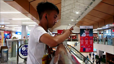 A teenager uses his smartphone to pass the time while inside a shopping center Footage