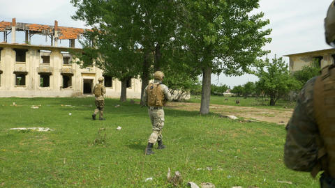 Army intervention troops assigned to patrol a rural area with buildings ravaged  Footage