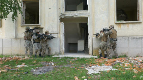 Camouflaged soldiers walking in an abandoned building with weapons during an ope Footage