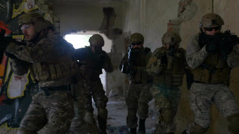 Group of soldiers moving fast through ruined building in search and rescue opera Footage