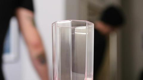 Closeup Transparent Glass Stands against Men Background Footage