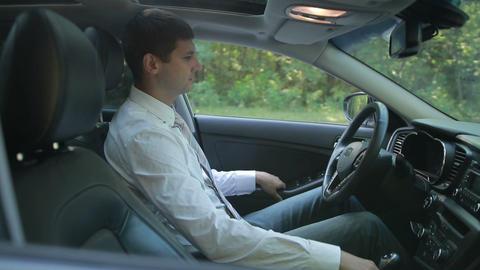 Businessman in car fastening seatbelt Footage