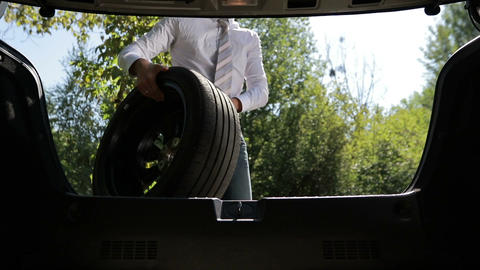 Businessman taking spare wheel out of car trunk Footage