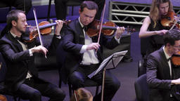 Orchestra with musicians who play music on stage Footage