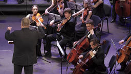 The conductor conducts violinists and cellists in the orchestra Footage