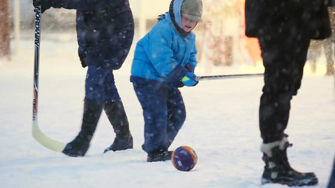 Slow Motion Adults with Child Play Hockey on Snow in Park Footage