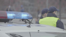 A police car with flashing lights. Police officers. Day Footage