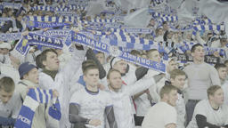 Fans during the match are holding scarves over their heads and singing Footage