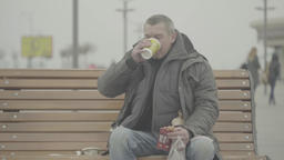 A homeless beggar is drinking tea on the street Footage