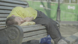 Homeless beggar asleep on a bench in the park Footage